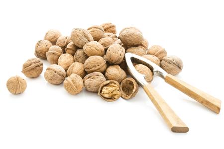Walnuts (Juglans regia) and nutcracker on white background