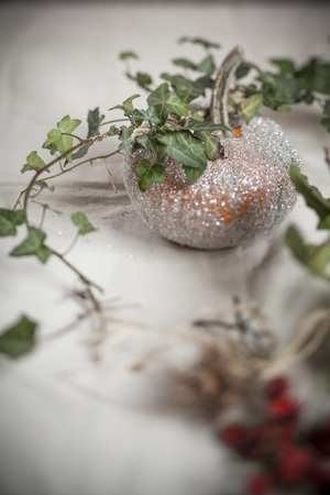 Halloween decoration,glittering pumpkin with ivy tendril on table LANG_EVOIMAGES
