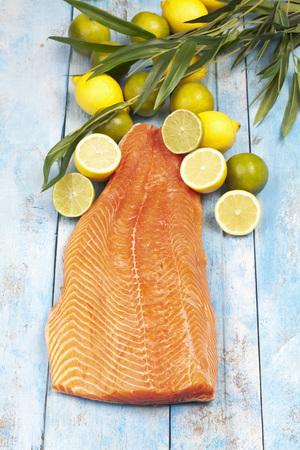Salmon fillet (Salmo salar) and lemons on blue wooden table LANG_EVOIMAGES