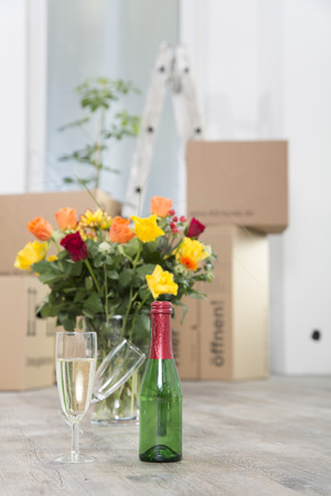 Cardboard boxes,champagne and bunch of flowers in new home