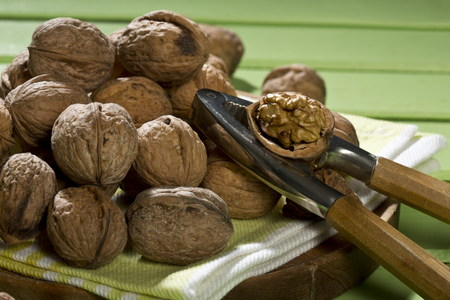 Walnuts (Juglans regia),nutcracker and napkin on green wooden table,close-up