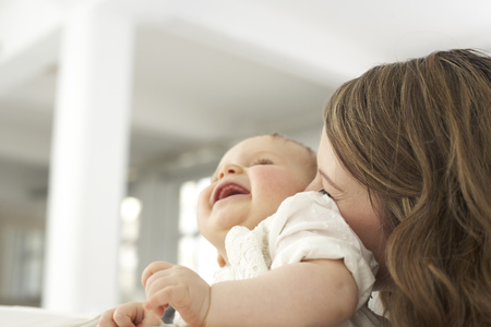 Mother kissing her laughing baby girl