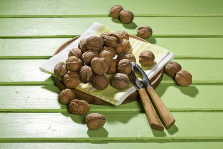 Walnuts (Juglans regia),nutcracker and napkin on green wooden table