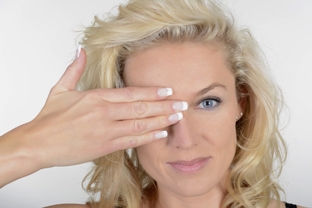 Blond woman with hand above eye,portrait LANG_EVOIMAGES