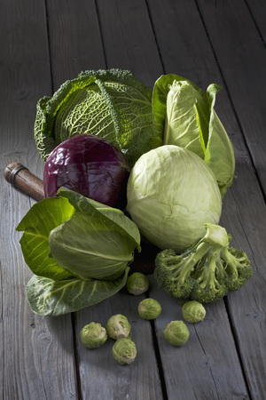 Cabbage varieties and antique knife on grey wooden table LANG_EVOIMAGES