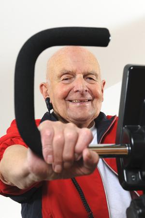 Portrait of old man training on exercise machine