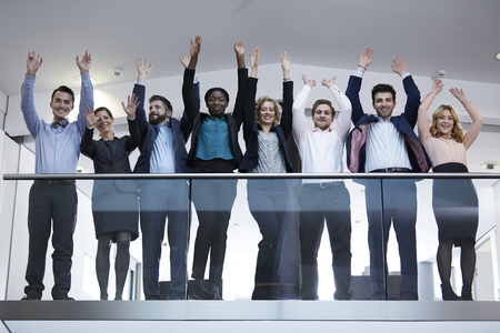 Germany,Neuss,Group of business people standing behind railing,raising arms