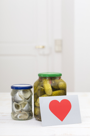 Glass of pickled cucumbers,a glass of rollmops and a postcard with red heart on white wooden table