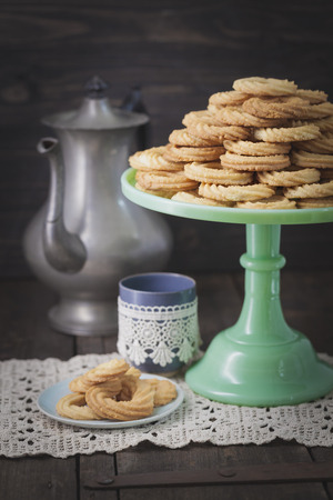 Traditional spritz cookies on green cake plate and coffeepot in background LANG_EVOIMAGES