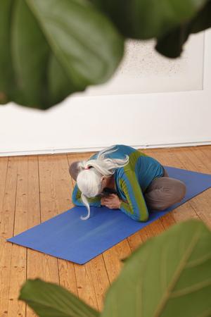 Germany,Dusseldorf,Senior woman practicing yoga