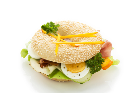 Sesame seed bagel garnished with slices of bacon,lettuce,cucumber,carrot,egg,Fol Epi and parsley