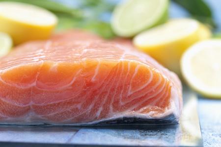 Salmon fillets (Salmo salar) and sliced lemons on blue wooden table