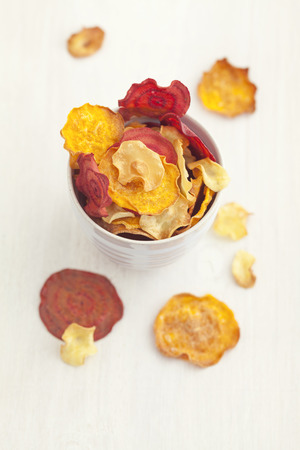 Bowl of roasted vegetable chips made of parsnips,sweet potatoes,beetroots,carrots and turnips