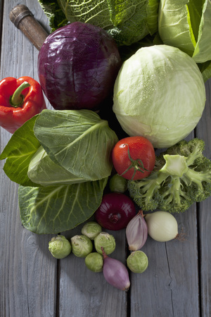 Cabbage varieties and other vegetables on grey wooden table