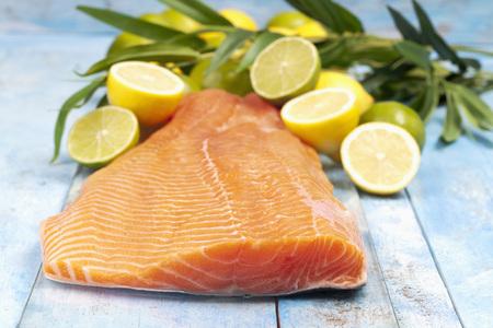 Salmon fillet (Salmo salar) and sliced lemons on blue wooden table LANG_EVOIMAGES
