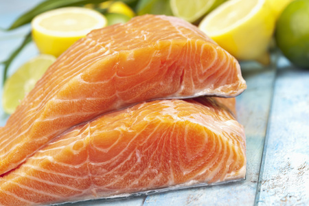 Salmon fillets (Salmo salar) and lemons on blue wooden table