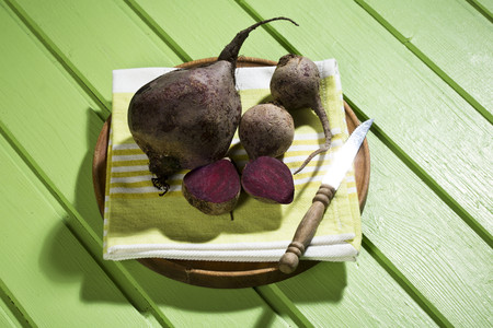 Sliced and whole beetroots (Beta vulgaris),wooden board,cloth and knife on green wooden table