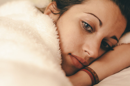 Young woman resting in bed and thinking about something