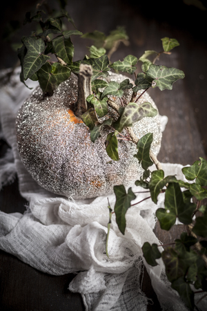 Halloween decoration,glittering pumpkin with ivy tendril on wooden table