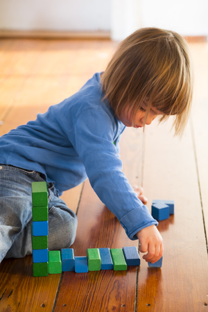 Little girl playing with blue aund green wooden building bricks LANG_EVOIMAGES