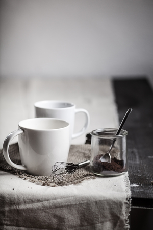 Two white mugs,wire whisk and a glass with cocoa on wooden table LANG_EVOIMAGES