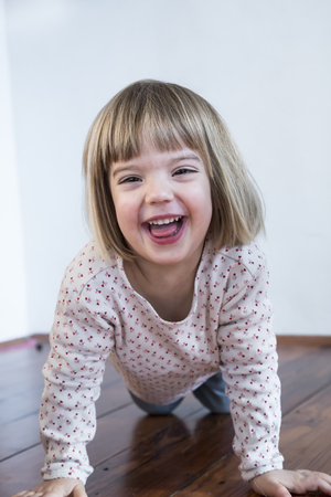 Portrait of smiling little girl on all fours