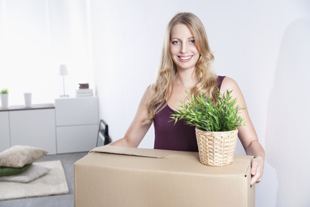 Smiling young woman carrying cardboard box