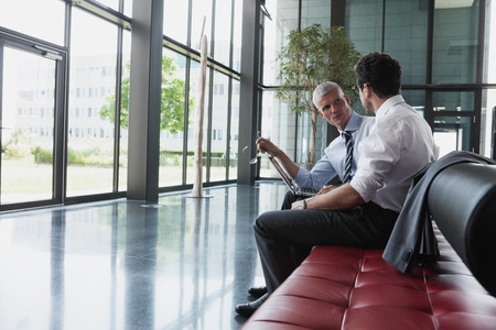 Germany,Businessmen talking in lobby LANG_EVOIMAGES