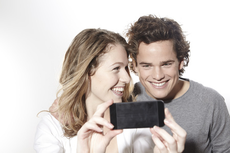 Portrait of happy young couple with smart phone,studio shot