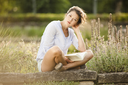 Woman sitting on stonewall reading a book