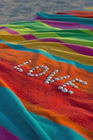 The word Love formed by shells lying on a multicolored bath towel
