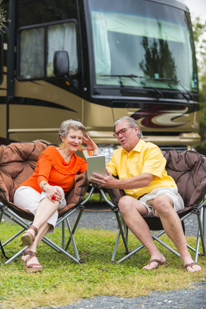 USA,Texas,Senior couple in front of their recreational vehicle using mini tablet pc