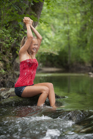 Austria, Salzkammergut, Mondsee, teenage girl refreshing at a brook