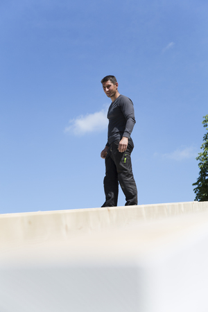 Construction of a residential house, man standing on roof LANG_EVOIMAGES