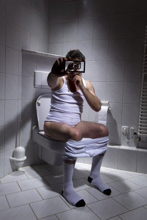 Germany, Man sitting on toilet, using smart phone
