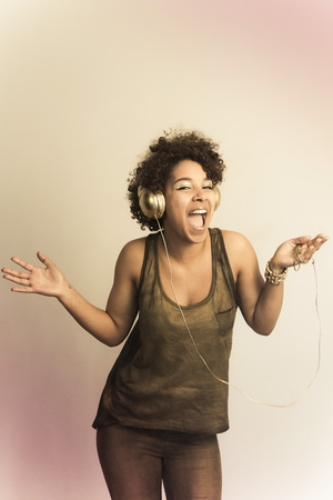 Portrait of dancing female Afro-American with headphones LANG_EVOIMAGES