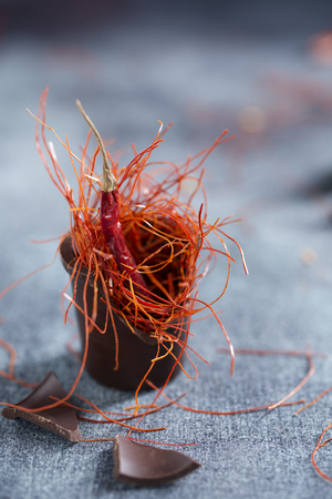 Chocolate cup with chili pod and saffron threads, ingredients for making chili chocolate, close-up