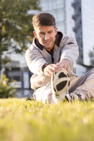 Poland, Warzawa, Young man doing warm up on grass