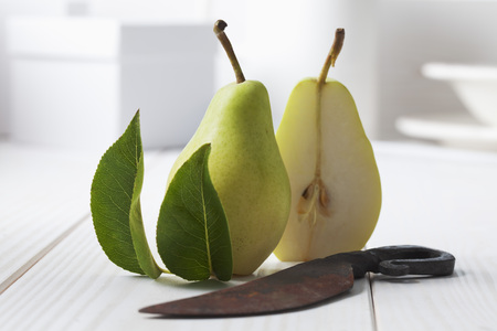 Two halfs of a pear (Pyrus), leaves and rusty knife on white wooden table