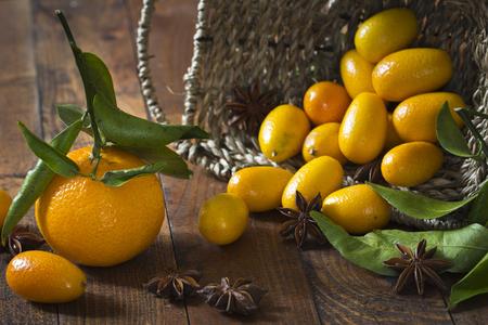 Tangerine (Citrus reticulata), kumquats and star anise (Illicium verum) on wooden table LANG_EVOIMAGES