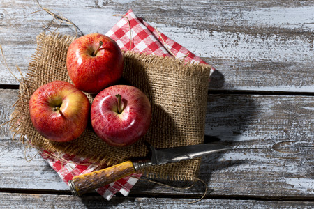 Three red apples and a knife on jute, cloth napkin and wooden table