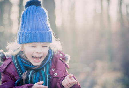Laughing boy wearing blue woolly hat