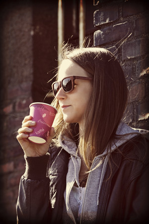 Young woman with sunglasses and coffee to go