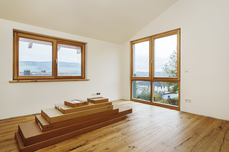 Room with finished oak parquet flooring and staple of cardboard boxes