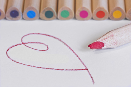 Row of colored pencils and drawn heart LANG_EVOIMAGES