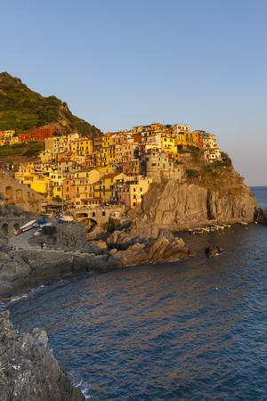 Italy, Cinque Terre, La Spezia Province, Liguria, Riomaggiore, Manarola, coast and houses, evening light LANG_EVOIMAGES