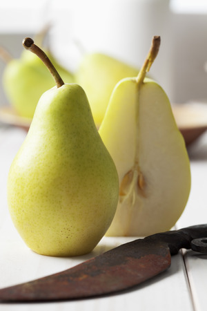 Two halfs of a pear (Pyrus) and rusty knife on white wooden table