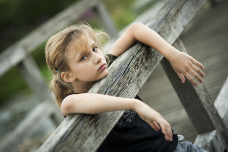 Portrait of serious looking girl at wooden boardwalk