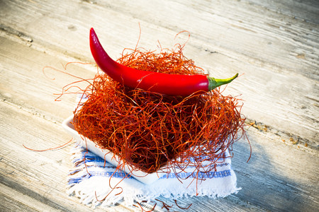 Bowl of red chili pepper and chili threads on dolly and wooden table