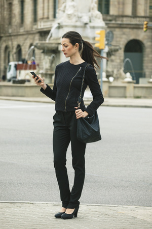 Spain, Catalunya, Barcelona, young black dressed businesswoman looking at her smartphone in front of a street LANG_EVOIMAGES